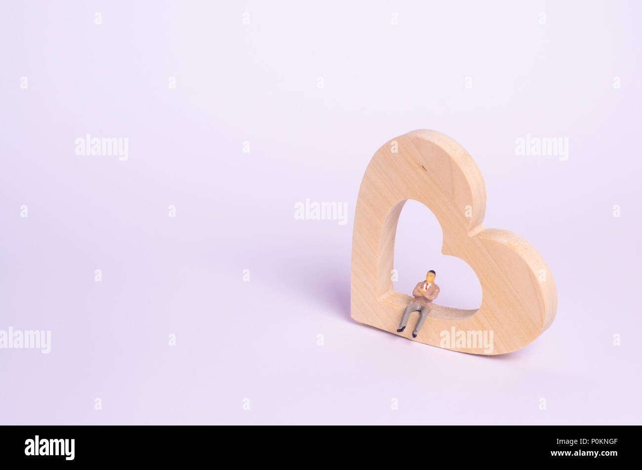 A Man Sits On A Wooden Heart And Waits A Lonely Person Is Looking