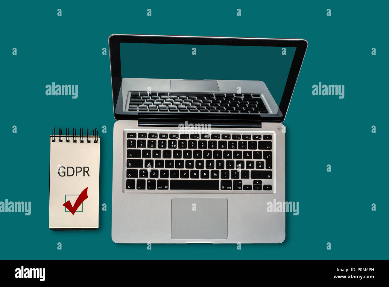 Top view of a laptop and a notepad with GDPR and a ticked checkbox on it, with copyspace - Stock Image