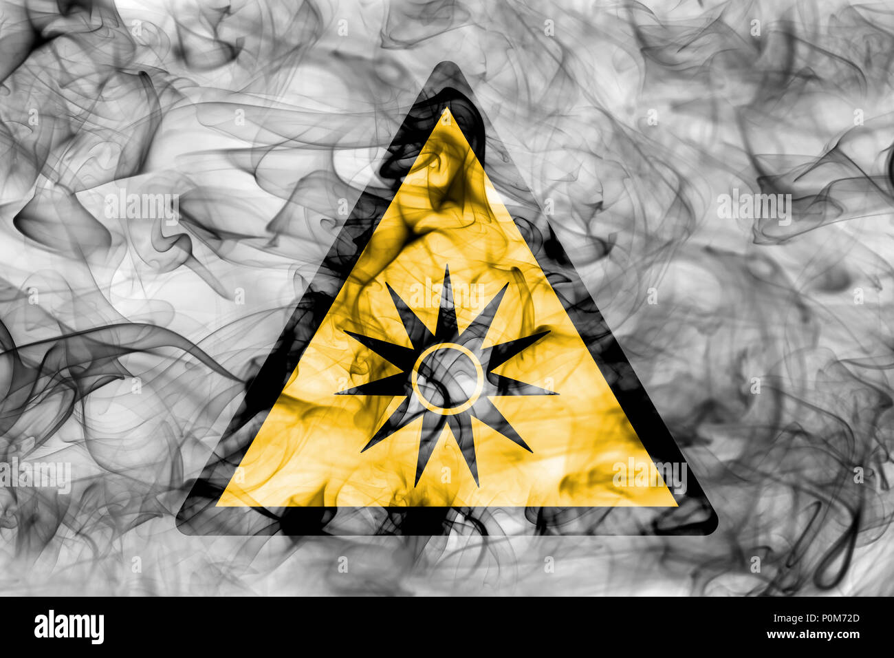 Optical radiation hazard warning smoke sign. Triangular warning hazard sign, smoke background. Stock Photo