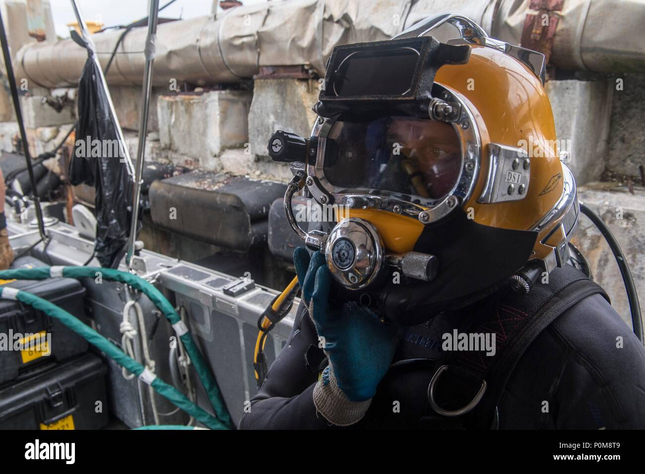 Construction Mechanic 2nd Class Andersen Gardner, from Fairport New York, attached to Underwater Construction Team (UCT) 2 performs dive operations in Apra Harbor, Guam June 6, 2018. UCT 2 specializes in the construction, inspection, maintenance, and repair of underwater and waterfront facilities in support of the Pacific Fleet. (U.S. Navy photo by Mass Communication Specialist 3rd Class Kryzentia Richards/Released) Stock Photo