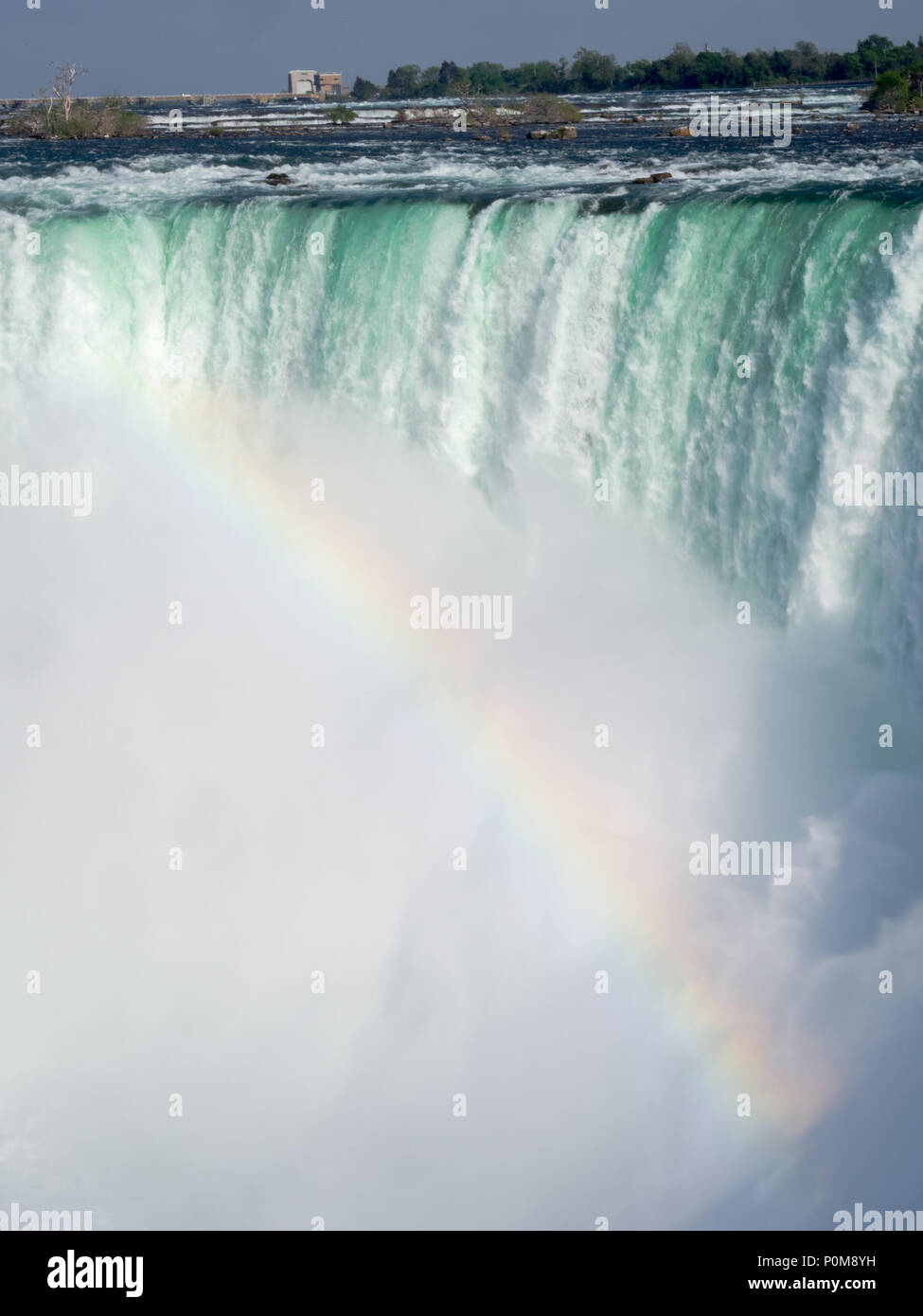 Niagara Horseshoe falls with a rainbow formed by falls. - Stock Image