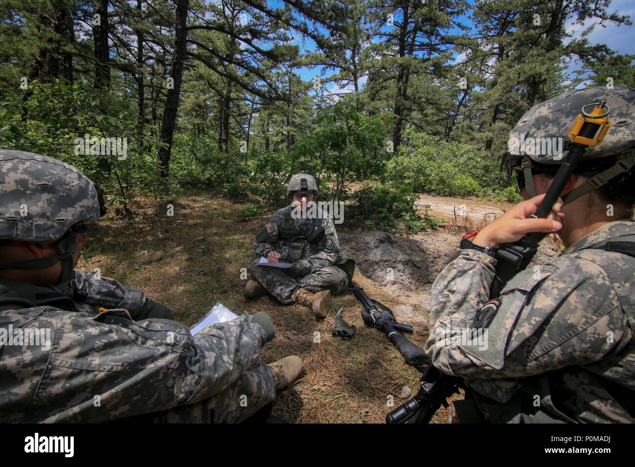 U.S. Army National Guard Soldiers from New Jersey's 250th Finance Detachment discuss sectors of fire during training on Joint Base McGuire-Dix-Lakehurst, N.J., June 5, 2018. The 250th Finance Detachment was trained in base defense by instructors from the U.S. Army's 174th Infantry Brigade. (U.S. Air National Guard photo by Master Sgt. Matt Hecht) - Stock Image