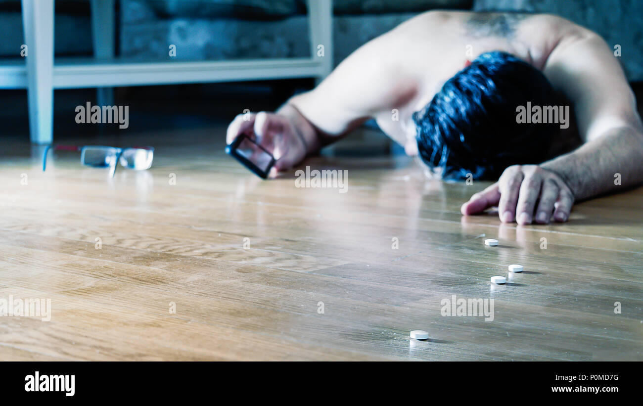 Mature man lying on the floor for overdose with pills calling for help using his mobile. - Stock Image