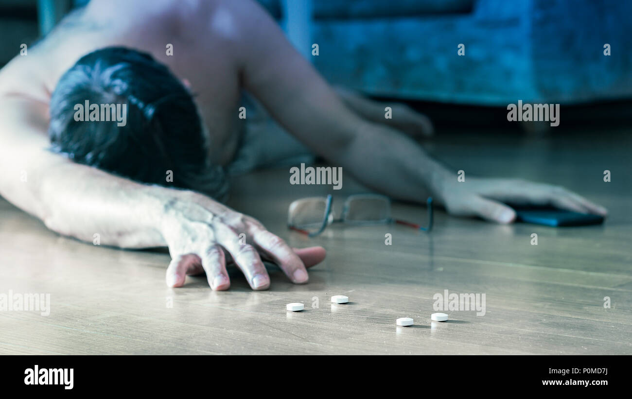 Suicide attemp concept: Mature man lying on the floor at home for overdose after pills. - Stock Image