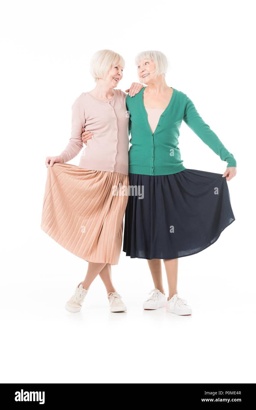 Smiling stylish senior women holding skirts isolated on white - Stock Image