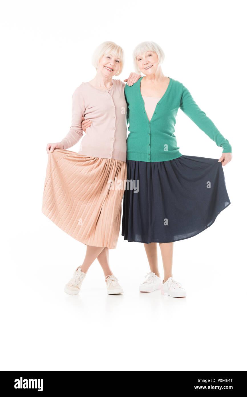 Portrait of smiling stylish senior women holding skirts isolated on white - Stock Image