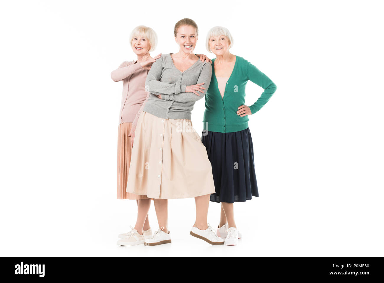Three stylish women in skirts standing isolated on white - Stock Image