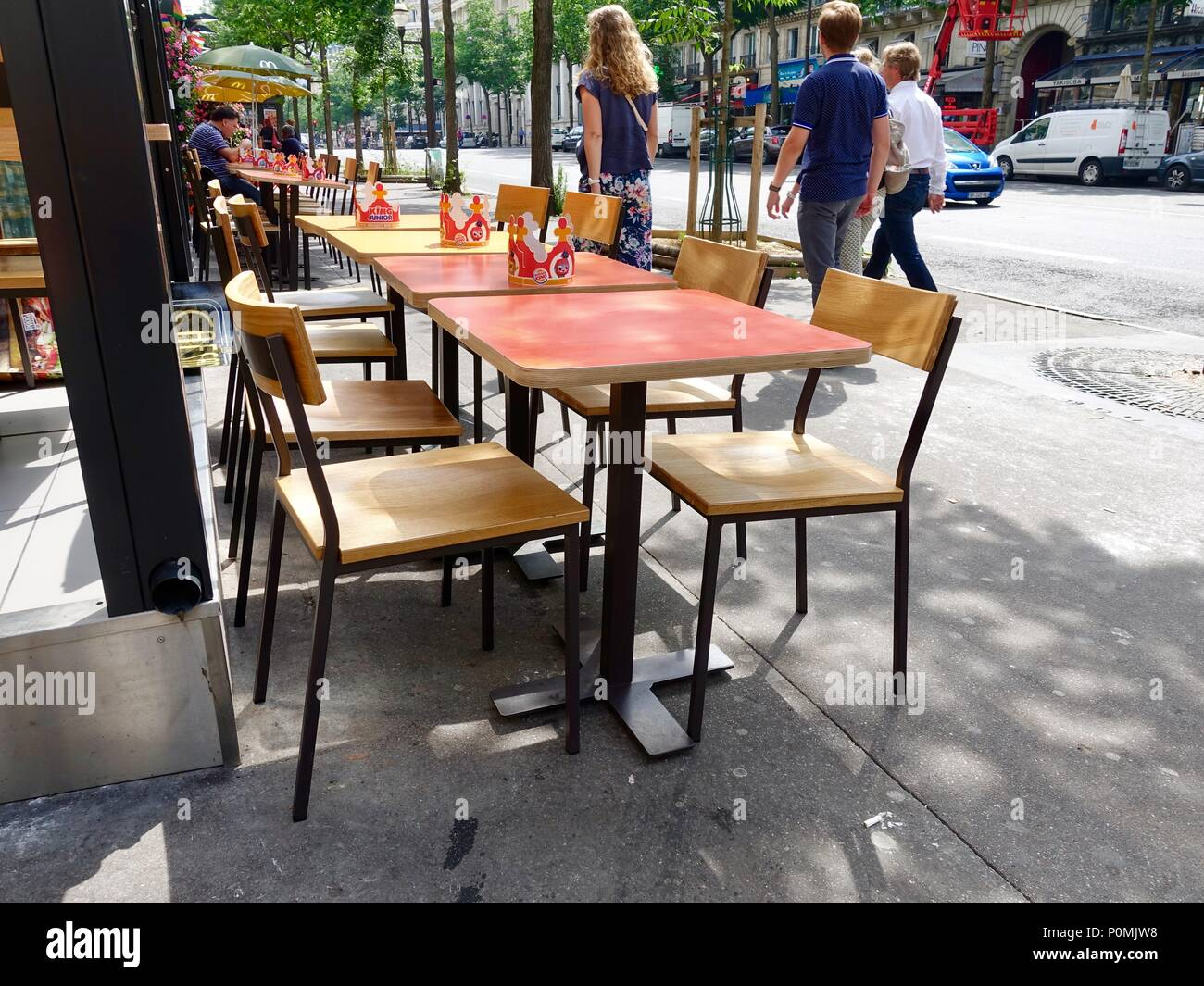 Tables, with Burger King crowns, and chairs set up outside a fast food restaurant, Paris, France - Stock Image