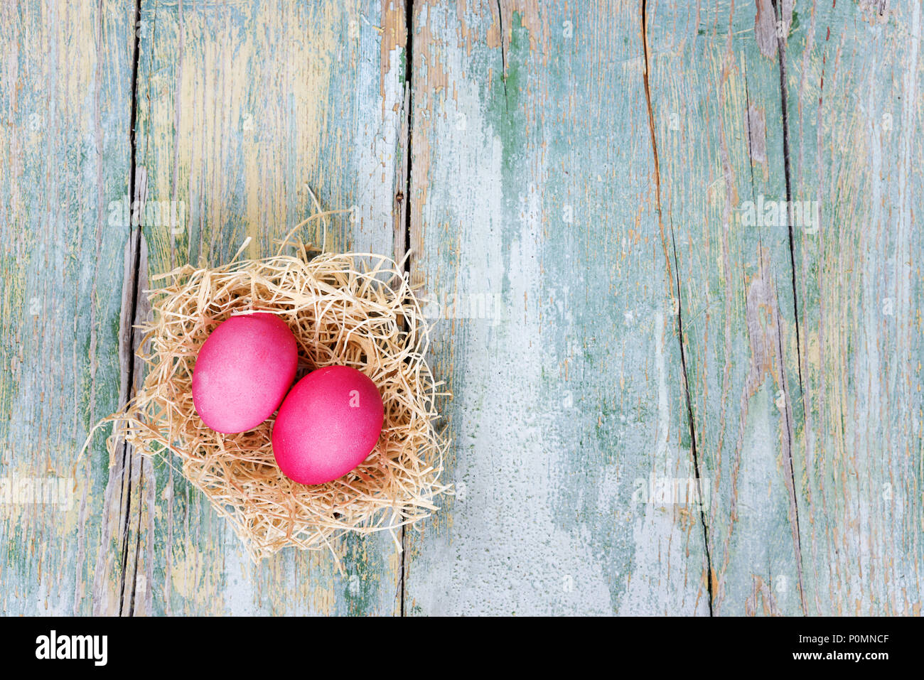 Easter composition with two red eggs in nest on the old blue wooden background, with copy-space, top view Stock Photo