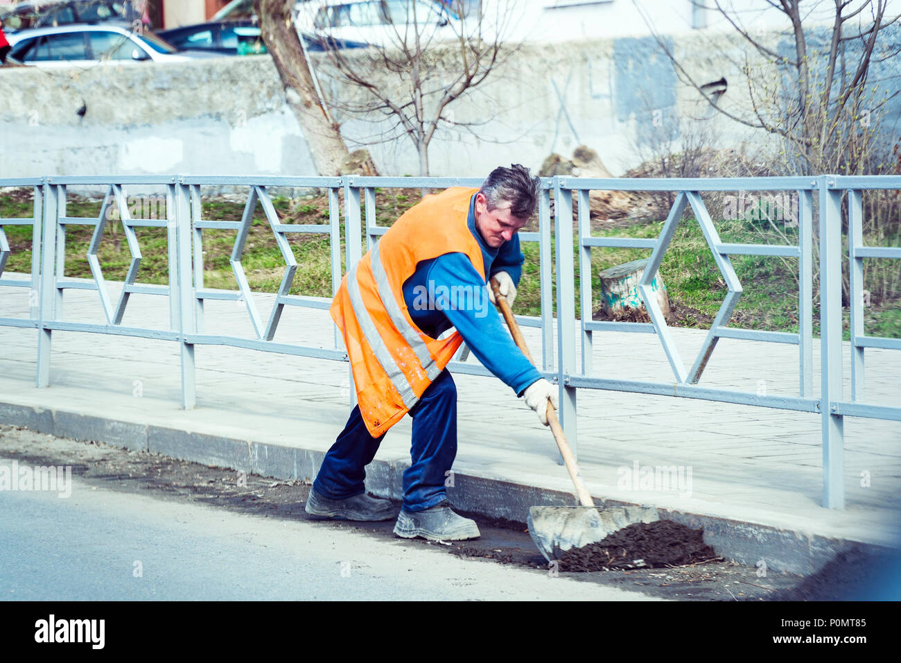 The janitor in an orange uniform cleans the garbage with a shovel on the city street - Stock Image