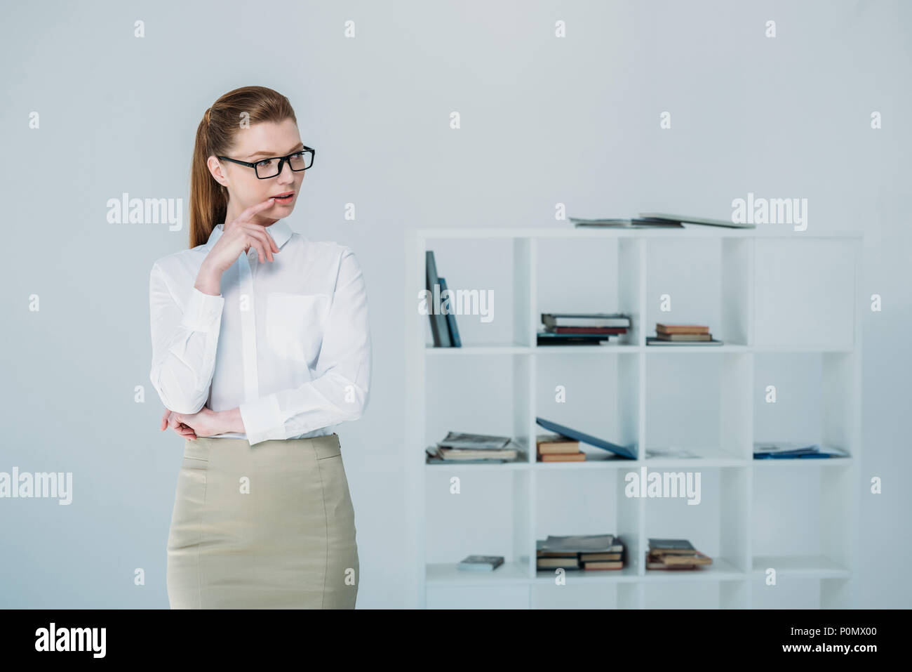 beautiful thoughtful businesswoman in formal wear and eyeglasses standing in modern office - Stock Image