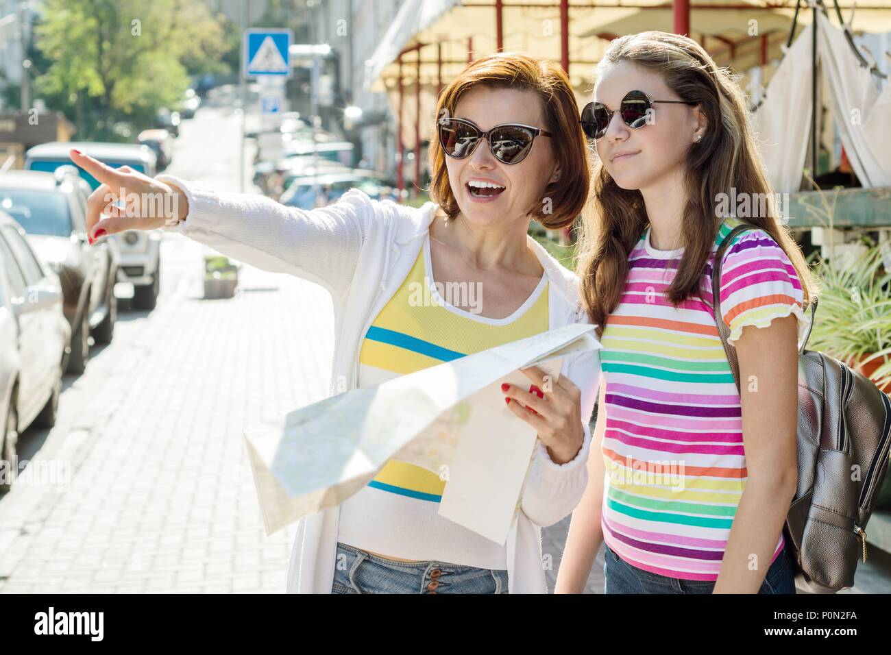 Mom and daughter teenager tourist looking at the map on the street of city - Stock Image