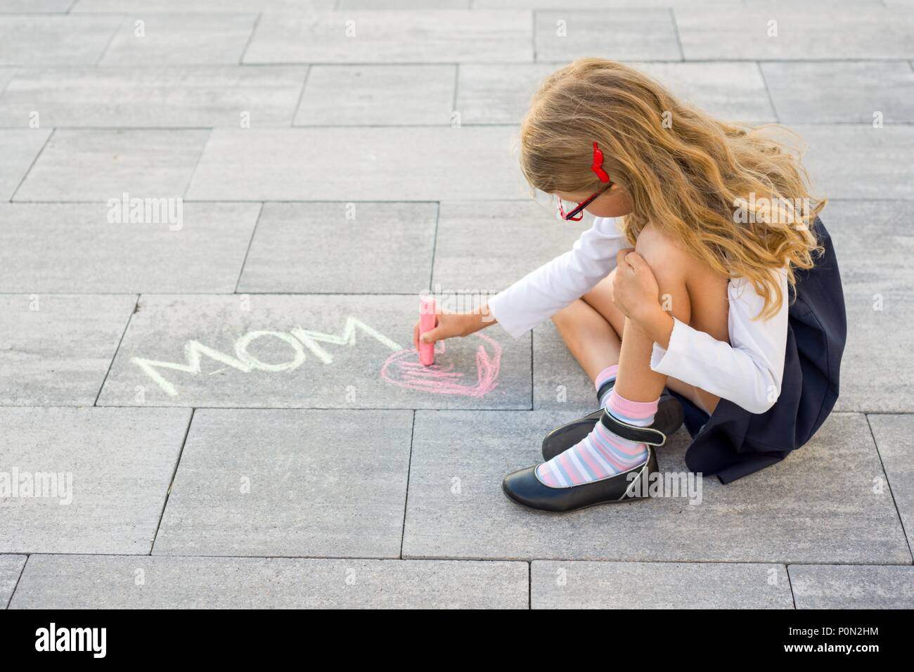 Picture gift for mother. A little girl draws colored crayons on the asphalt. Love mom. Mothers day Stock Photo