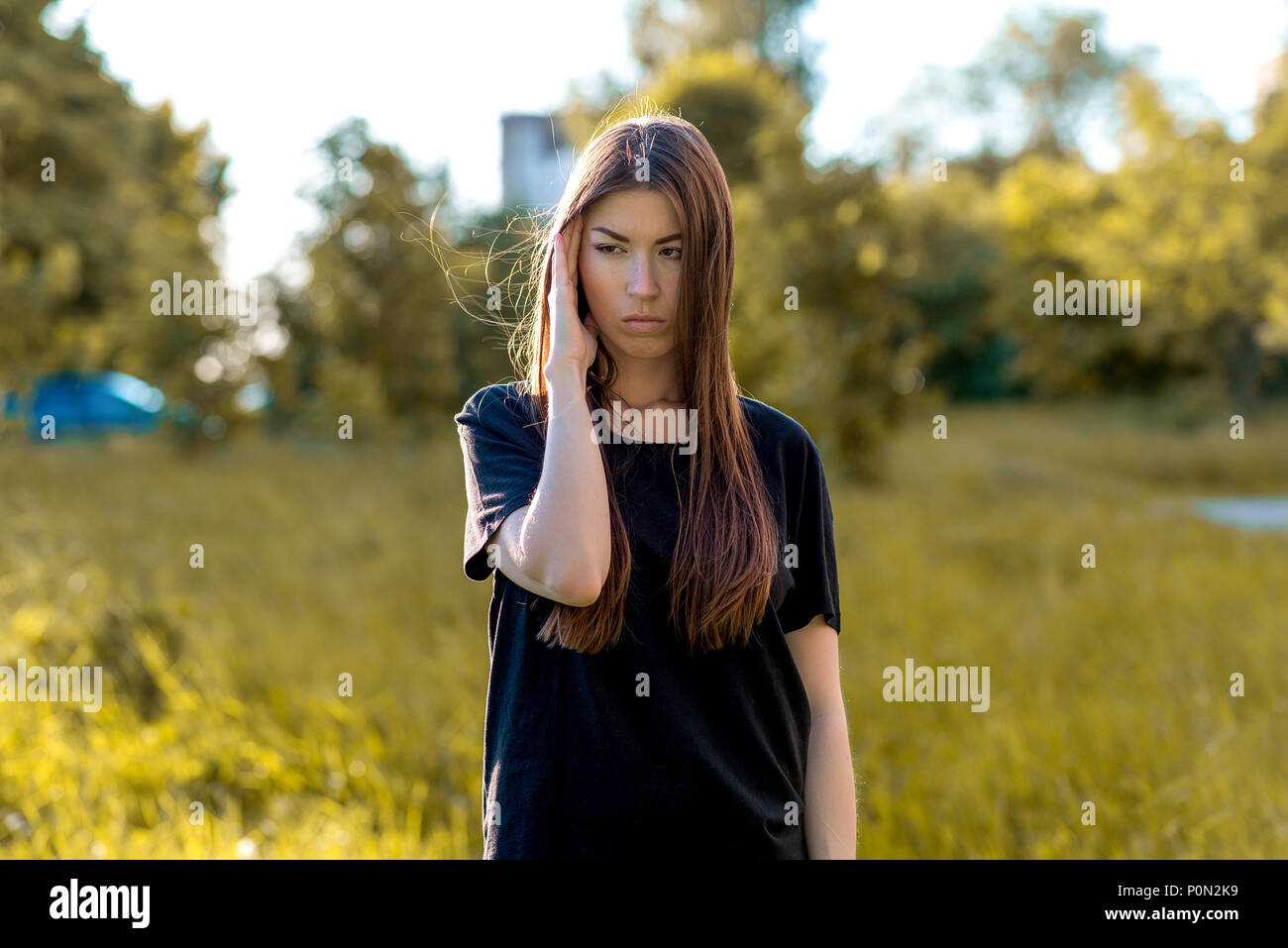 A brunette girl in the fresh air in a black T-shirt. He presses his hand with his temple. Emotions a headache. Migraines and bad thoughts. - Stock Image