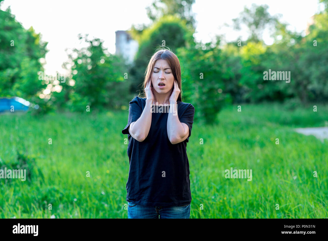 Girl in summer in a park in nature. Emotionally keeps his ears from loud sound. Squeezed her eyes open. Emotionally dissatisfaction with noise. Casual wear. - Stock Image