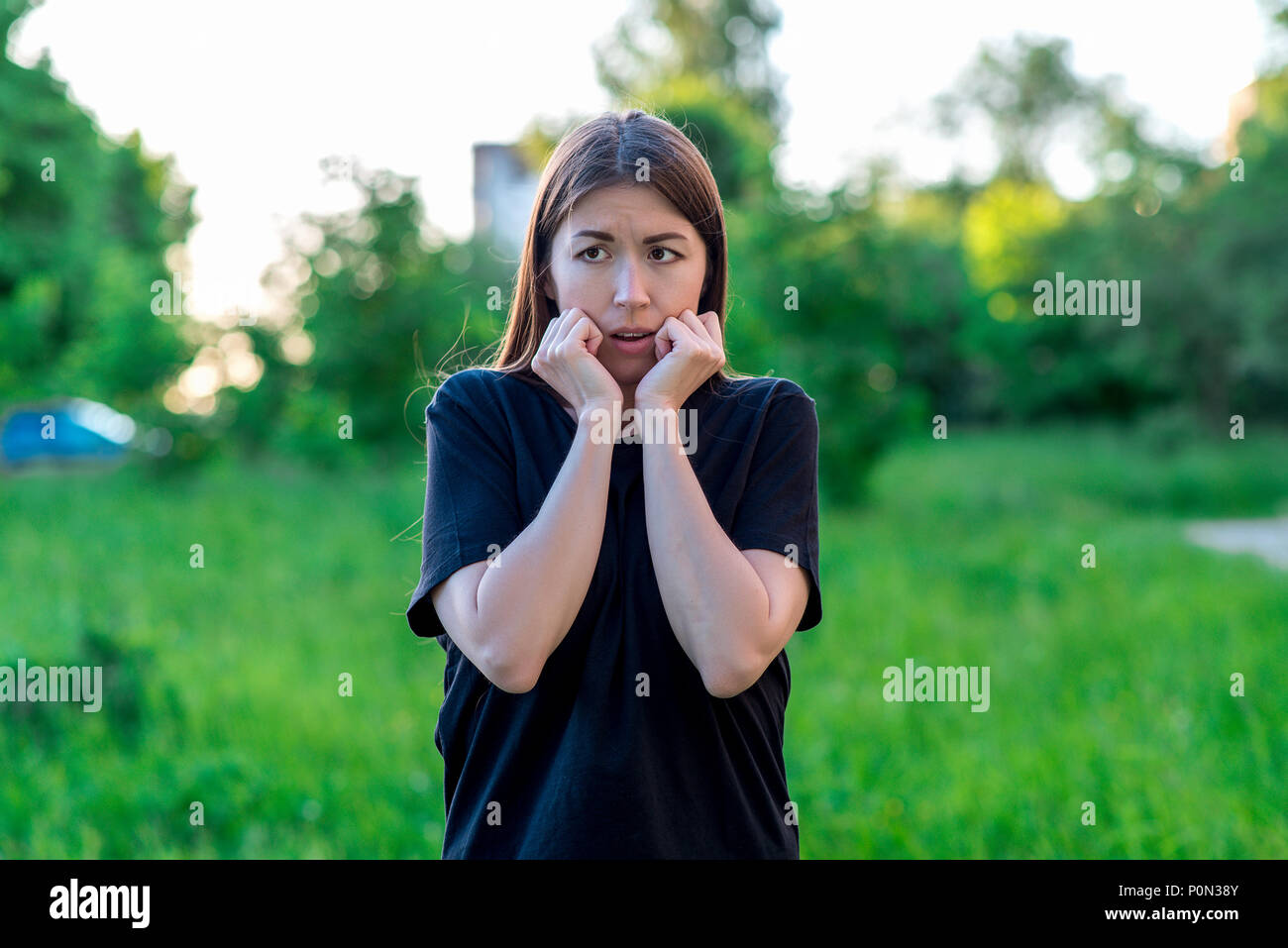 Beautiful brunette girl in summer in a park on nature. Emotional expression of fear. Gesture with hands shows emotional fear. Surprised face frightened eyes. - Stock Image