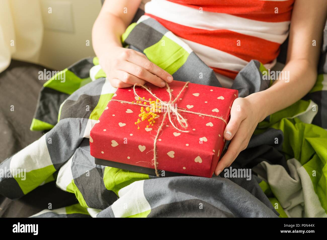 Gift in the hands. Packed in crafting paper with red hearts, decorated with a branch of yellow mimosa flowers. Spring gift - Stock Image