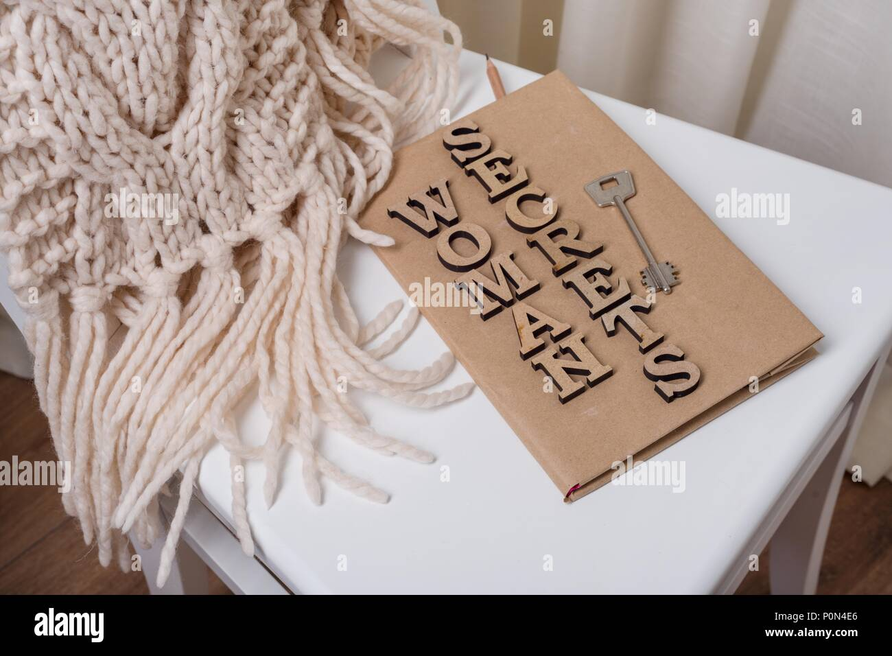 The book is wrapped in old paper and signed with wooden letters woman secrets, on the book key. White background chair in the interior of the house. - Stock Image