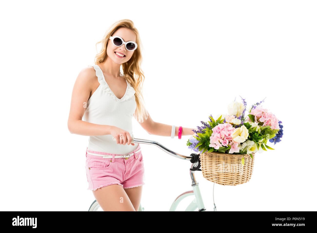 Blonde woman in sunglasses holding bicycle with flowers in basket isolated on white - Stock Image