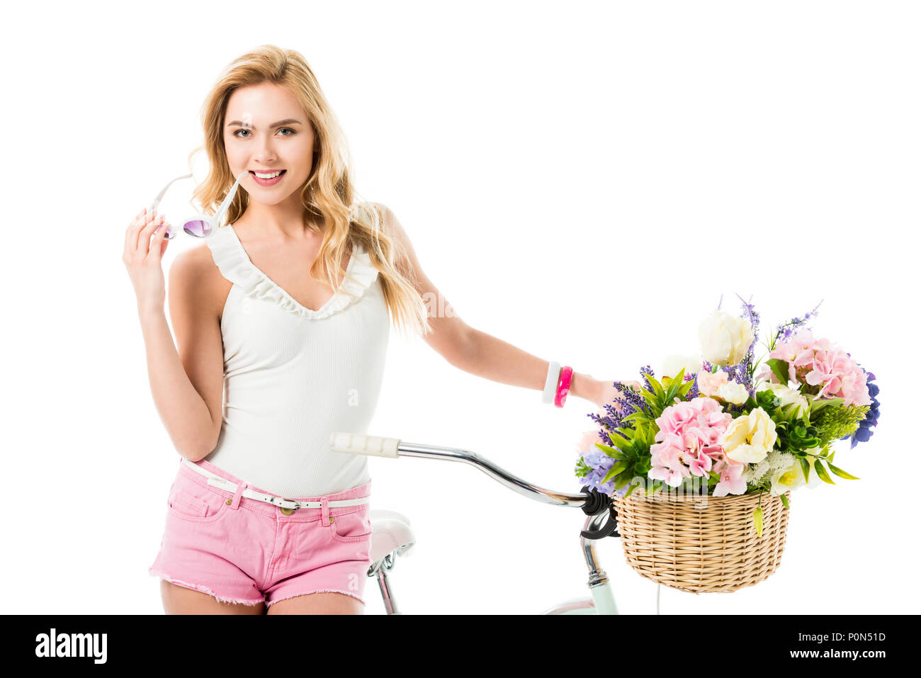 Attractive young woman standing by bicycle with flowers in basket isolated on white - Stock Image