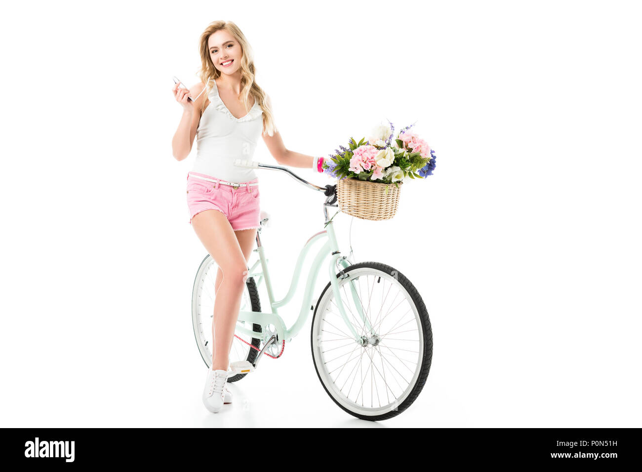 Blonde woman standing by bicycle with flowers in basket isolated on white - Stock Image