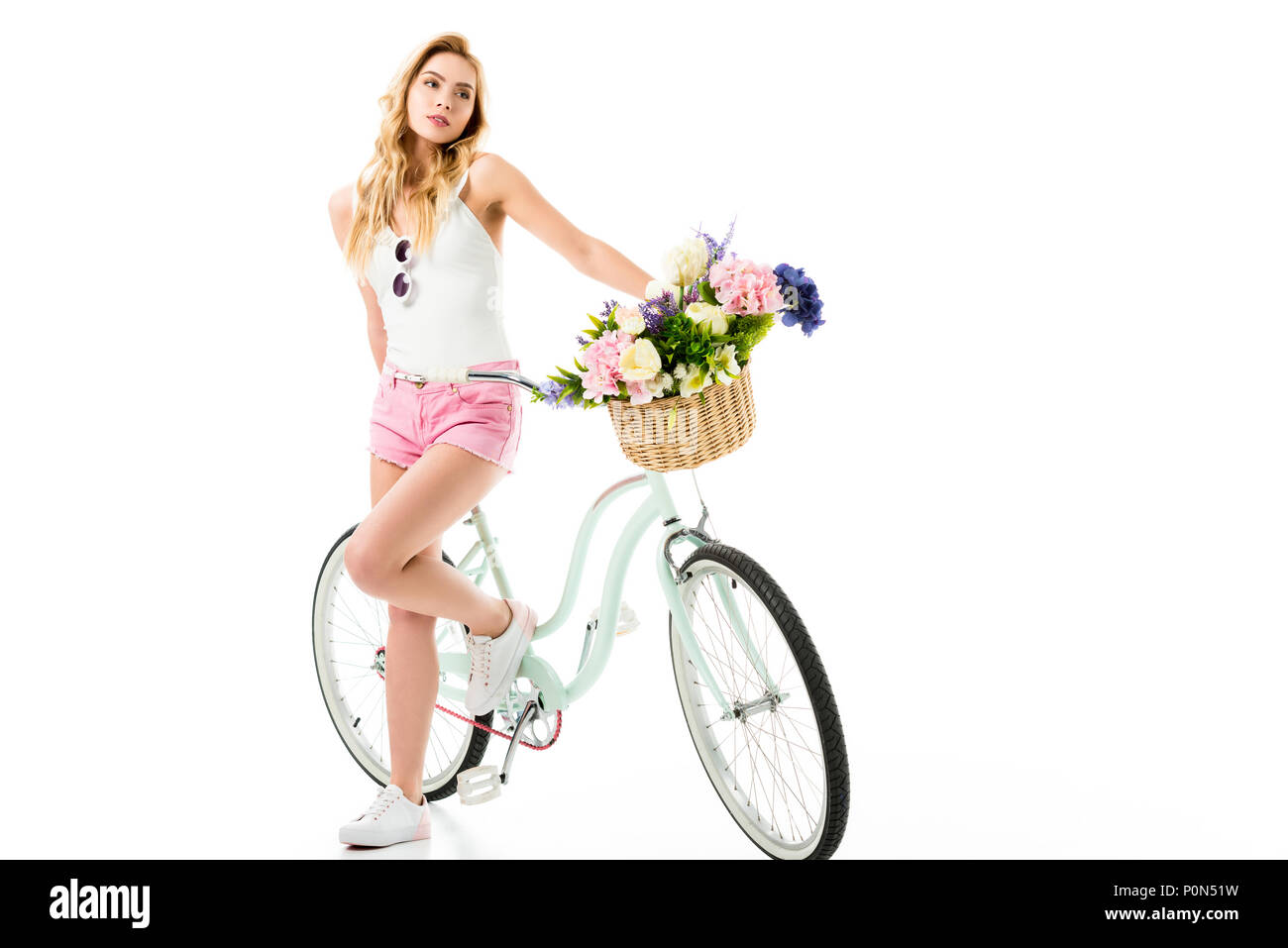 Young girl standing by cruiser bicycle with flowers in basket isolated on white - Stock Image