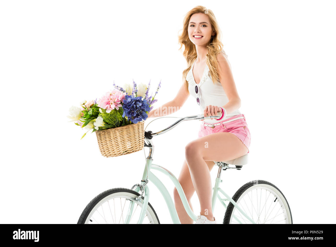 Attractive young woman riding bicycle with flowers in basket isolated on white - Stock Image