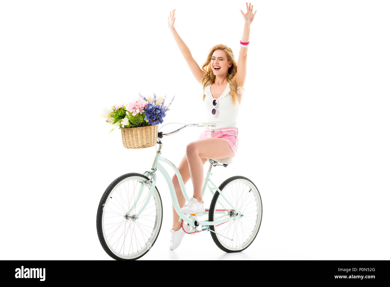 Blonde woman riding bicycle with flowers in basket isolated on white - Stock Image