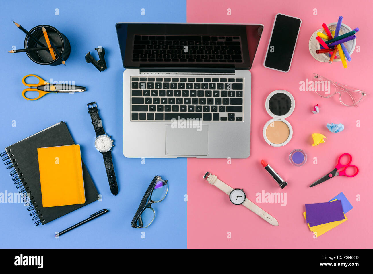 top view of laptop, smartphone and cosmetics with office supplies divided at male and female workplace - Stock Image