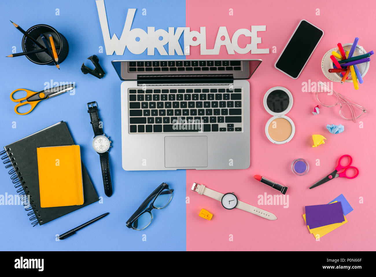 top view of laptop, smartphone, inscription workplace and cosmetics with office supplies divided at male and female workplace - Stock Image