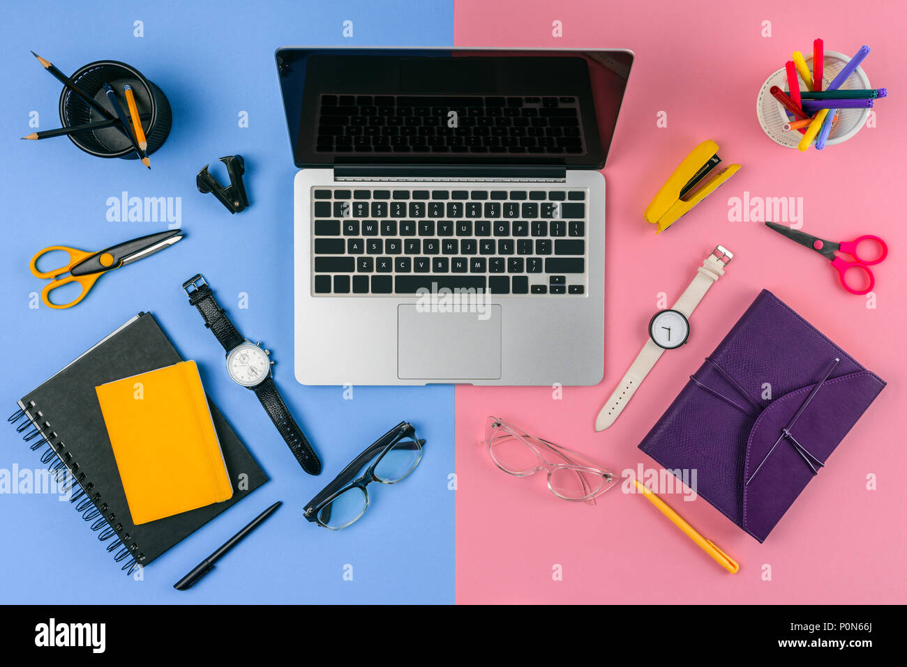 top view of laptop with blank screen, eyeglasses, wristwatches and notebooks divided at male and female workplace - Stock Image