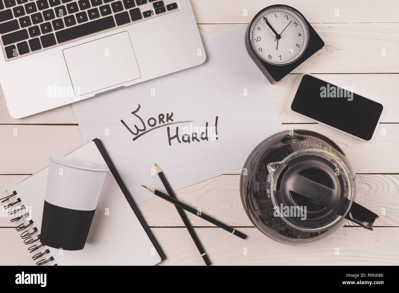 laptop, coffee pot, paper cup, clock, smartphone and inscription work hard at workplace - Stock Image