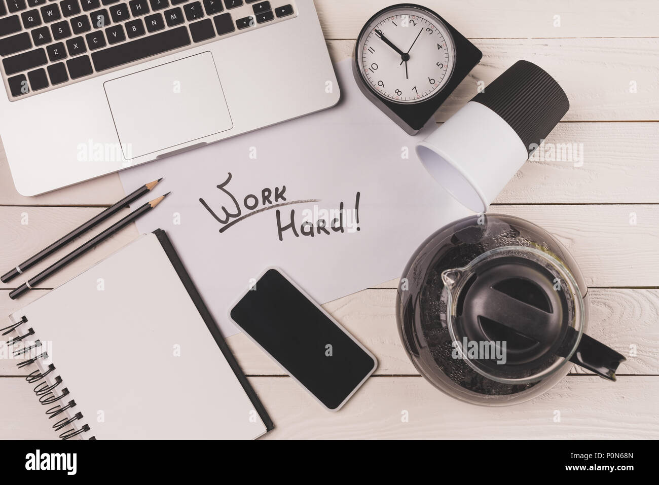 top view of laptop, coffee pot, paper cup, clock, smartphone and inscription work hard at workplace - Stock Image