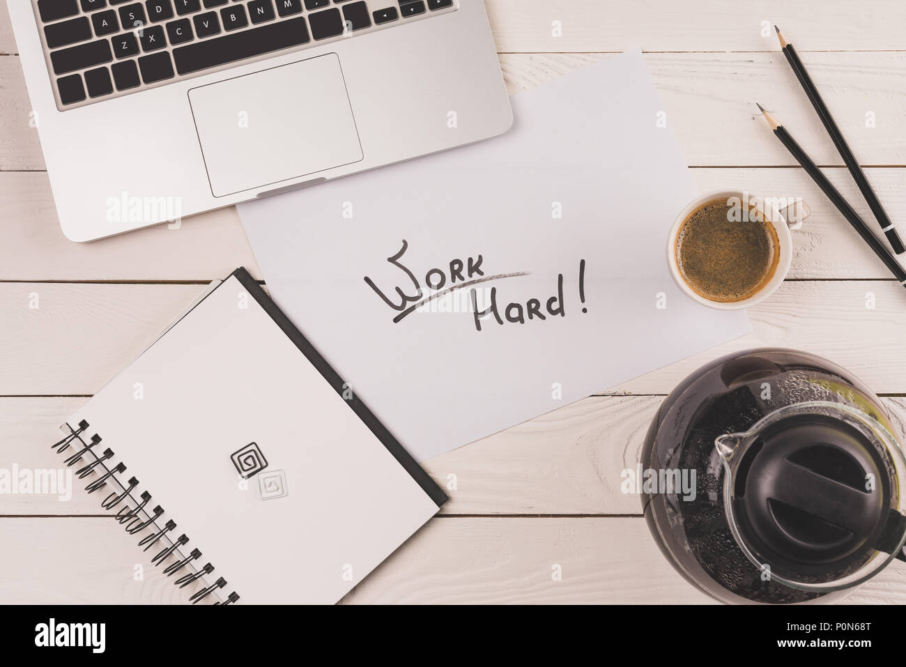 top view of laptop, clock, coffee and inscription work hard on paper at workplace - Stock Image