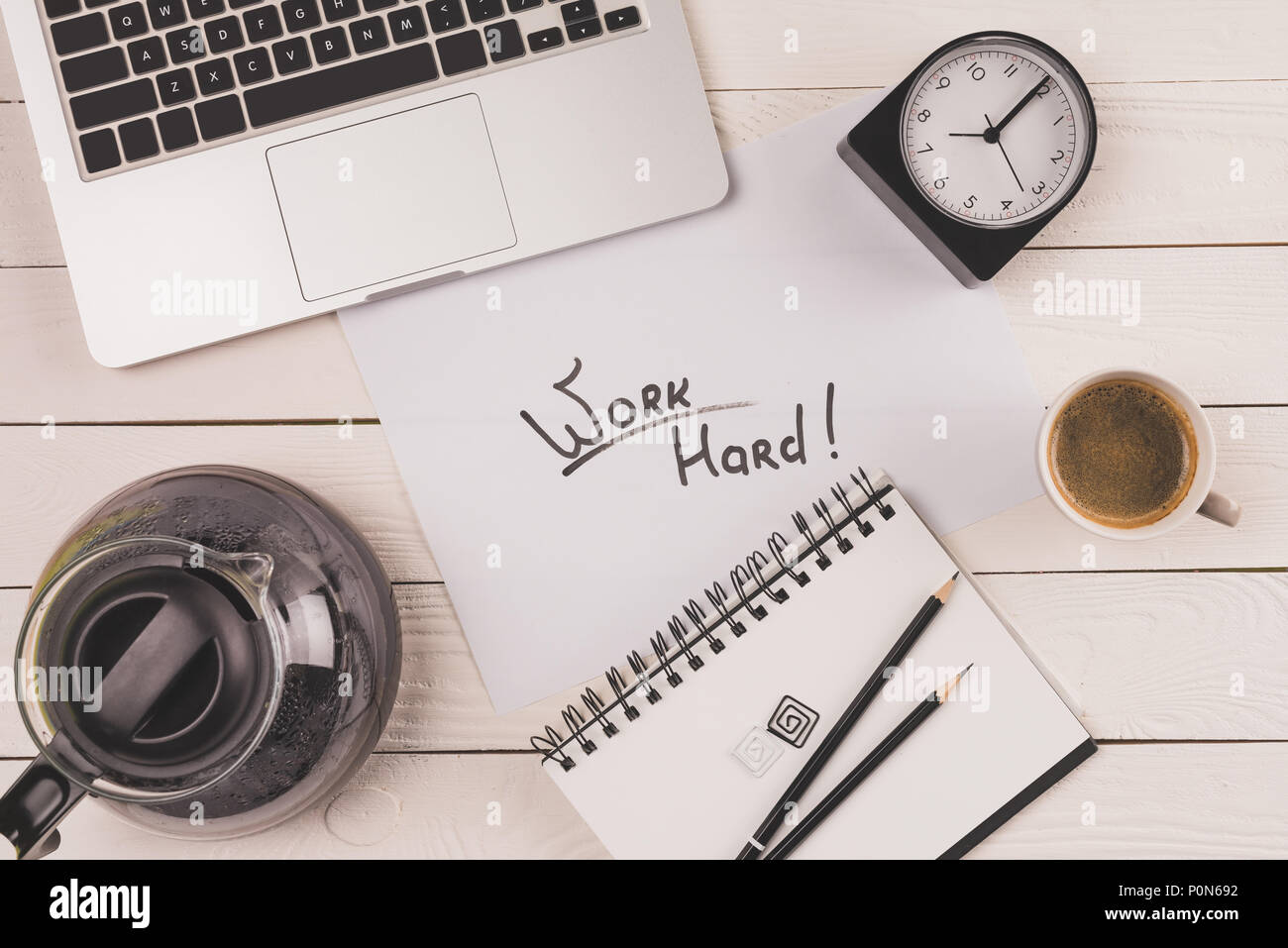 top view of laptop, clock, coffee and inscription work hard in notebook - Stock Image