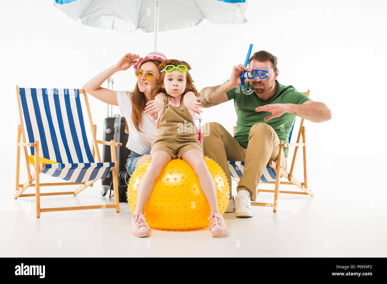 Family in swimming goggles depicting swim with sunshade, sun loungers and ball isolated on white, travel concept - Stock Image