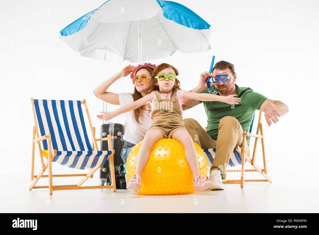 Family in swimming goggles with sunshade, sun loungers and ball isolated on white - Stock Image