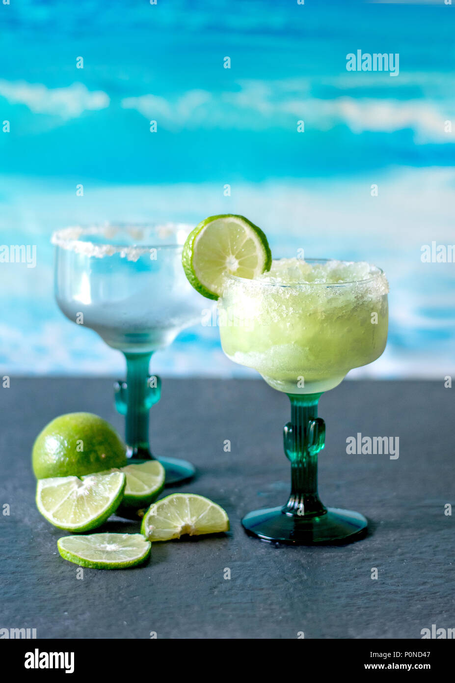 cold and icy frozen margarita drinks with slices of lime - Stock Image