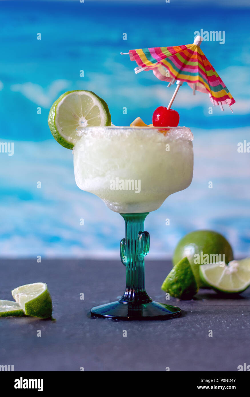 delicious frozen margarita drinks with lime and cherry garnish and a colorful drink umbrella Stock Photo