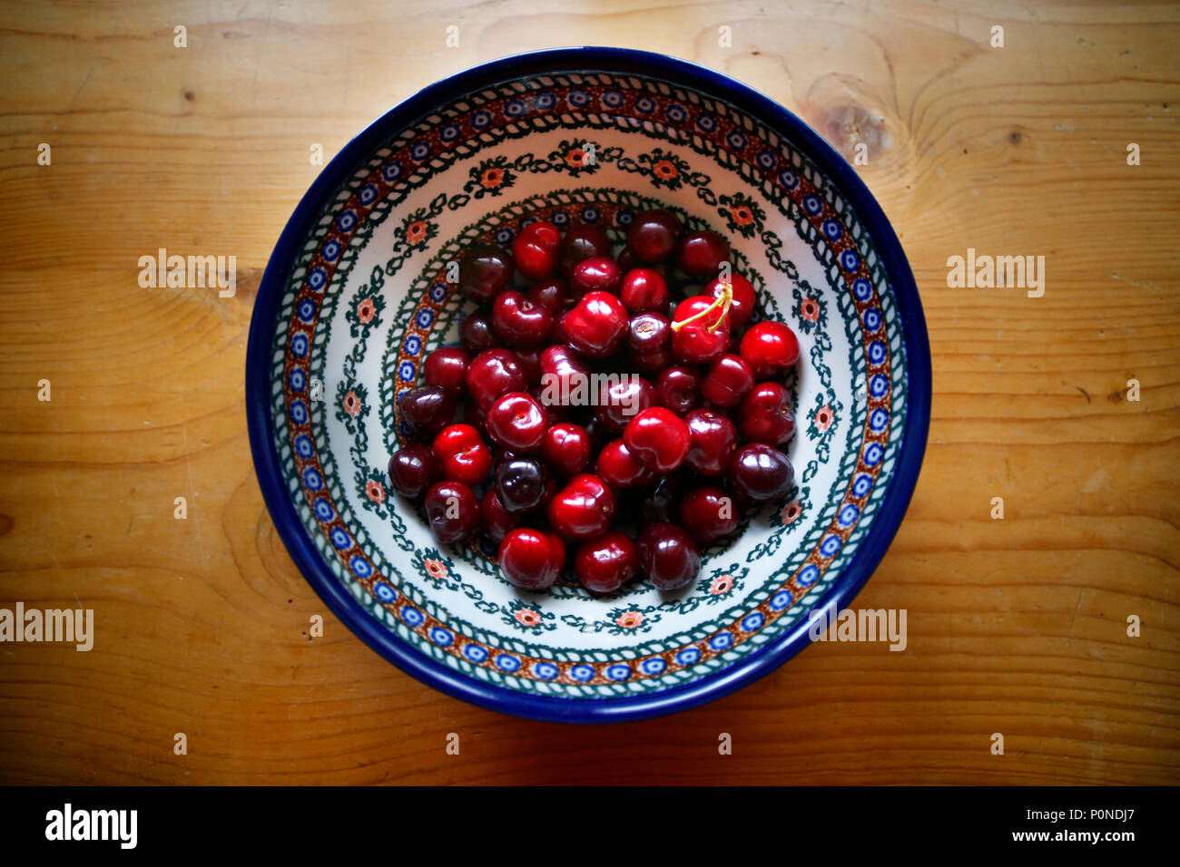 Bowl of cherries on an old pine table. - Stock Image