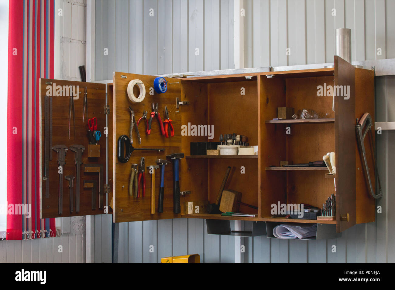 Open wooden cupboard with working tools - Stock Image
