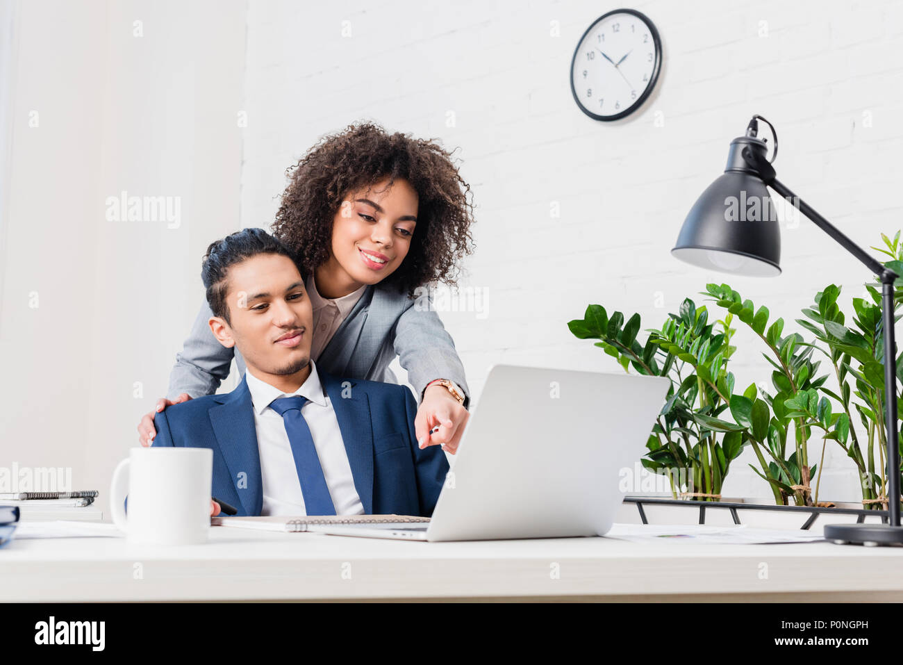 African american woman showing something on laptop screen to her male colleague - Stock Image
