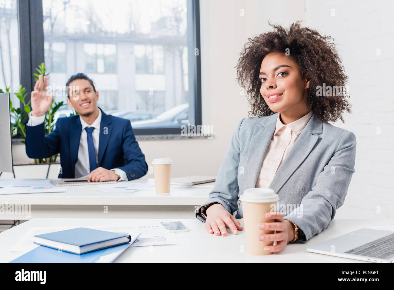 Businessman greeting someone by businesswoman holding coffee cup in office - Stock Image