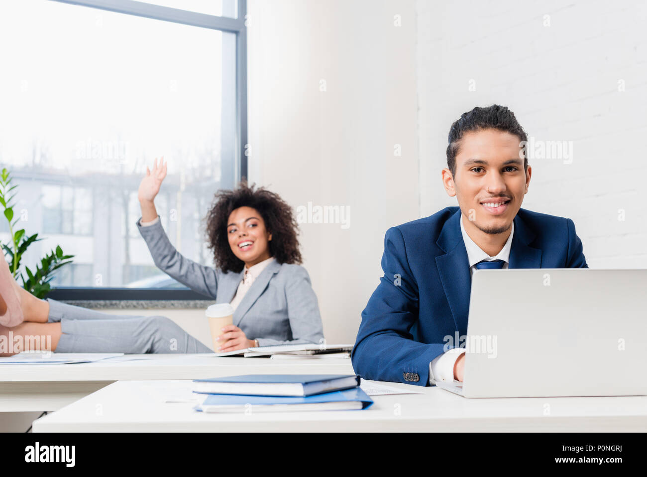 Businesswoman with paper cup greeting someone by businessman working on laptop in office - Stock Image