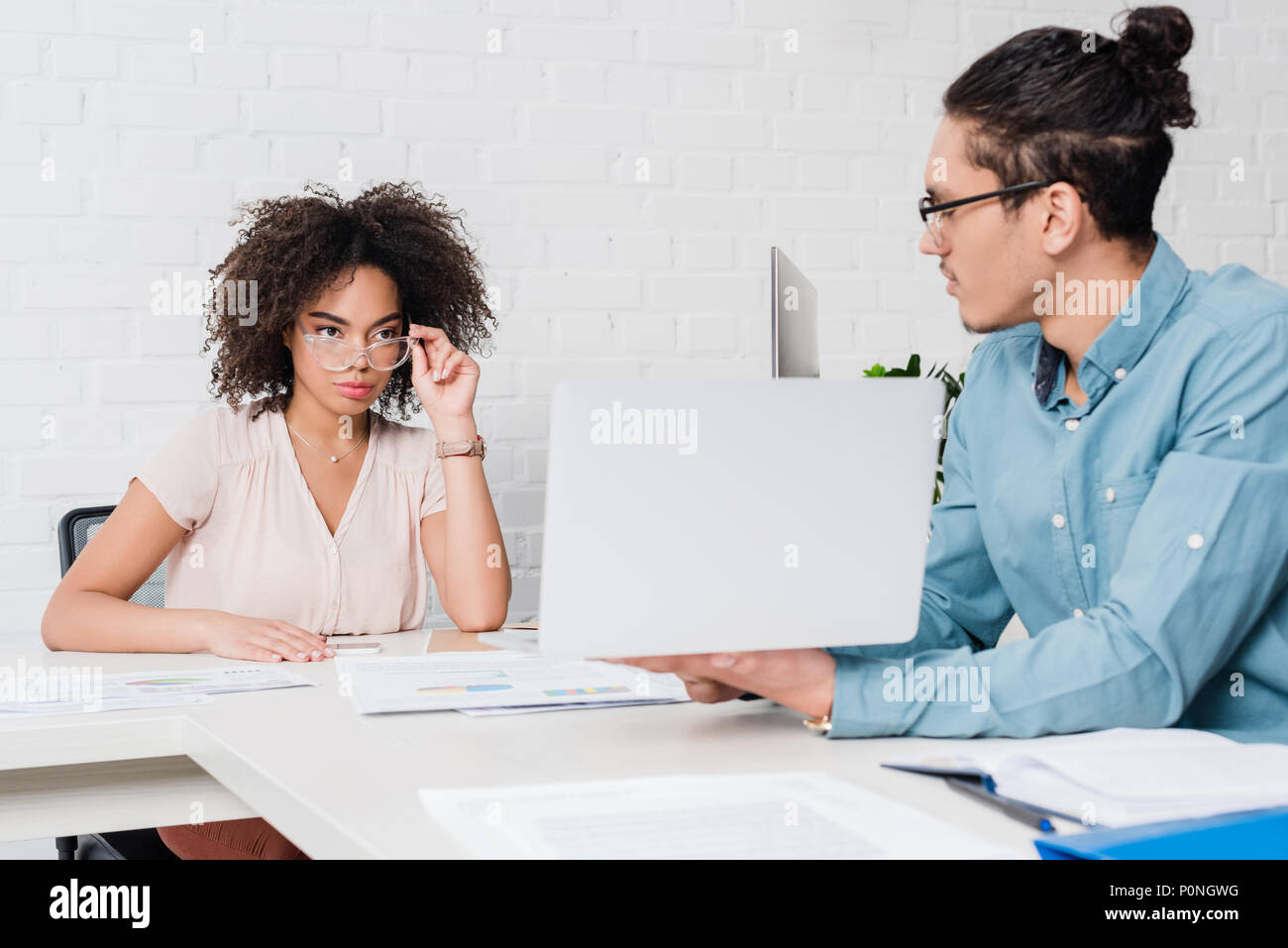 Businessman showing something on laptop to african american businesswoman in office - Stock Image