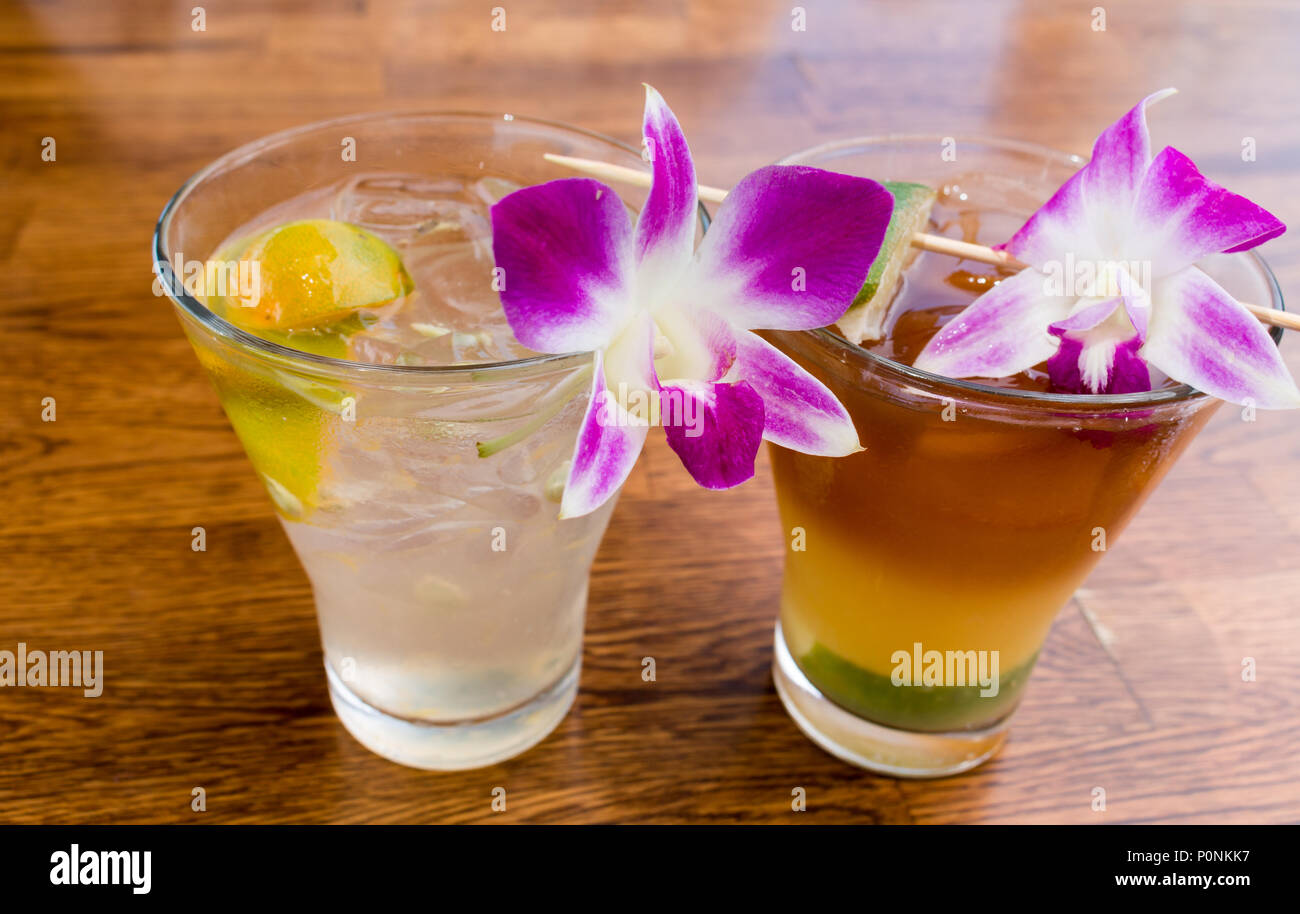 Tropical cocktails with orchid garnishes served at the Aloha Mixed Plate in Lahaina, Maui. - Stock Image