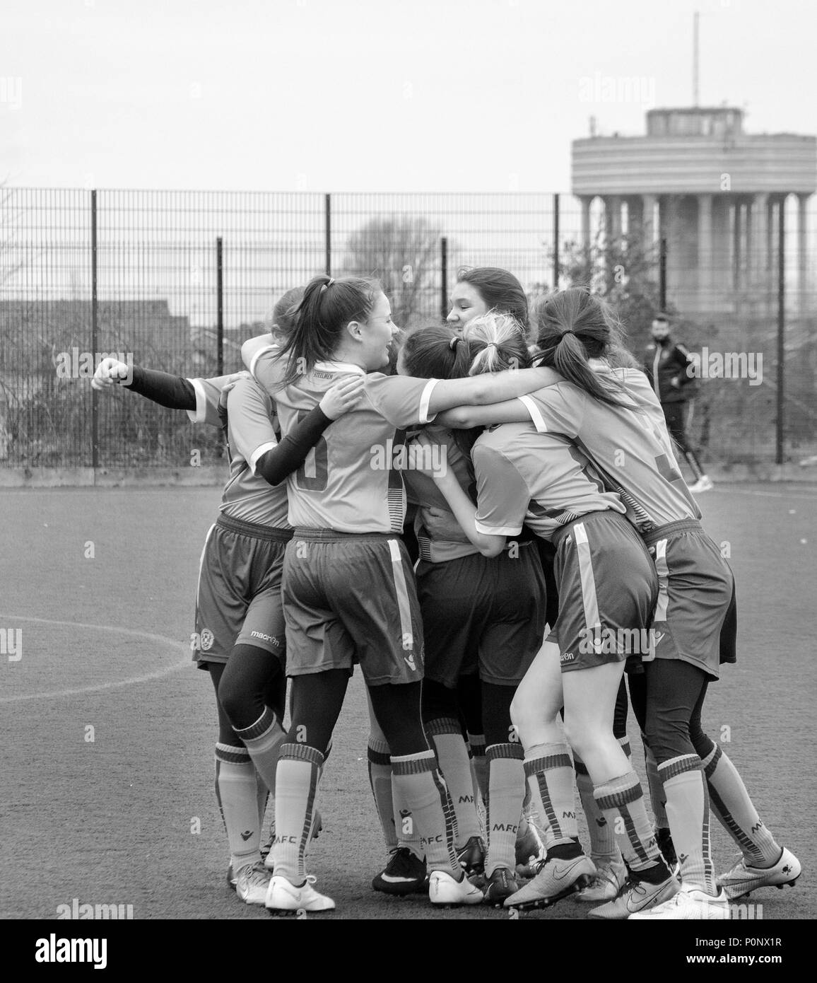 MOTHERWELL, SCOTLAND - MARCH 14th 2015: A girls youth football team surprises a win with a huddle. Stock Photo