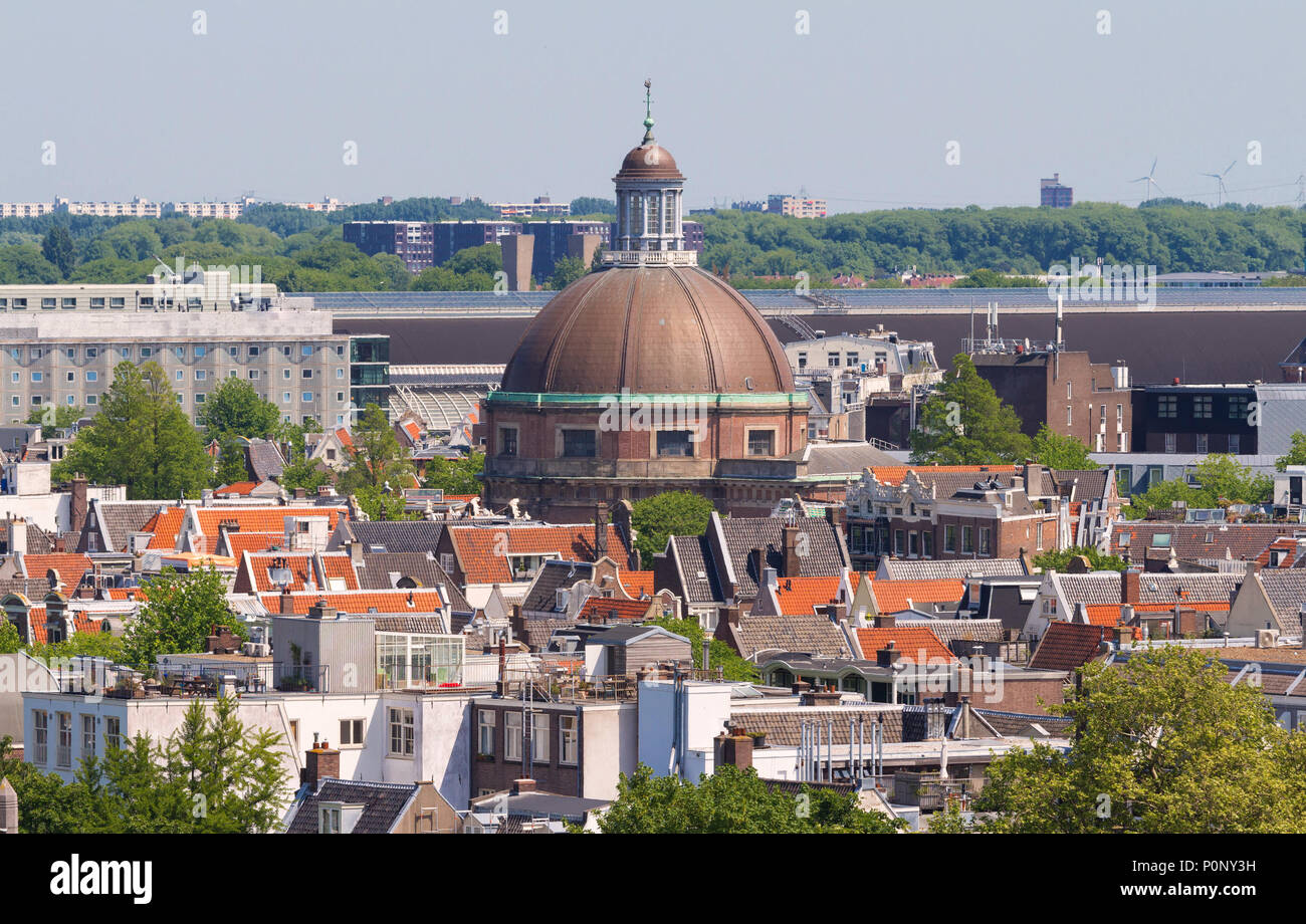 Round Koepelkerk with copper dome next to Singel canal . Roofs and facades of Amsterdam. City view from the bell tower of the church Westerkerk, Holland, Netherlands. - Stock Image