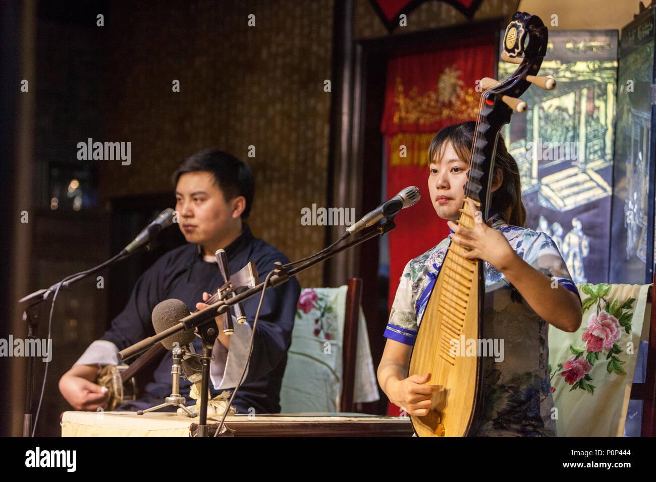 Suzhou, Jiangsu, China.  Young Woman Playing a Pipa, Young Man Playing a 'Three Strings.' - Stock Image