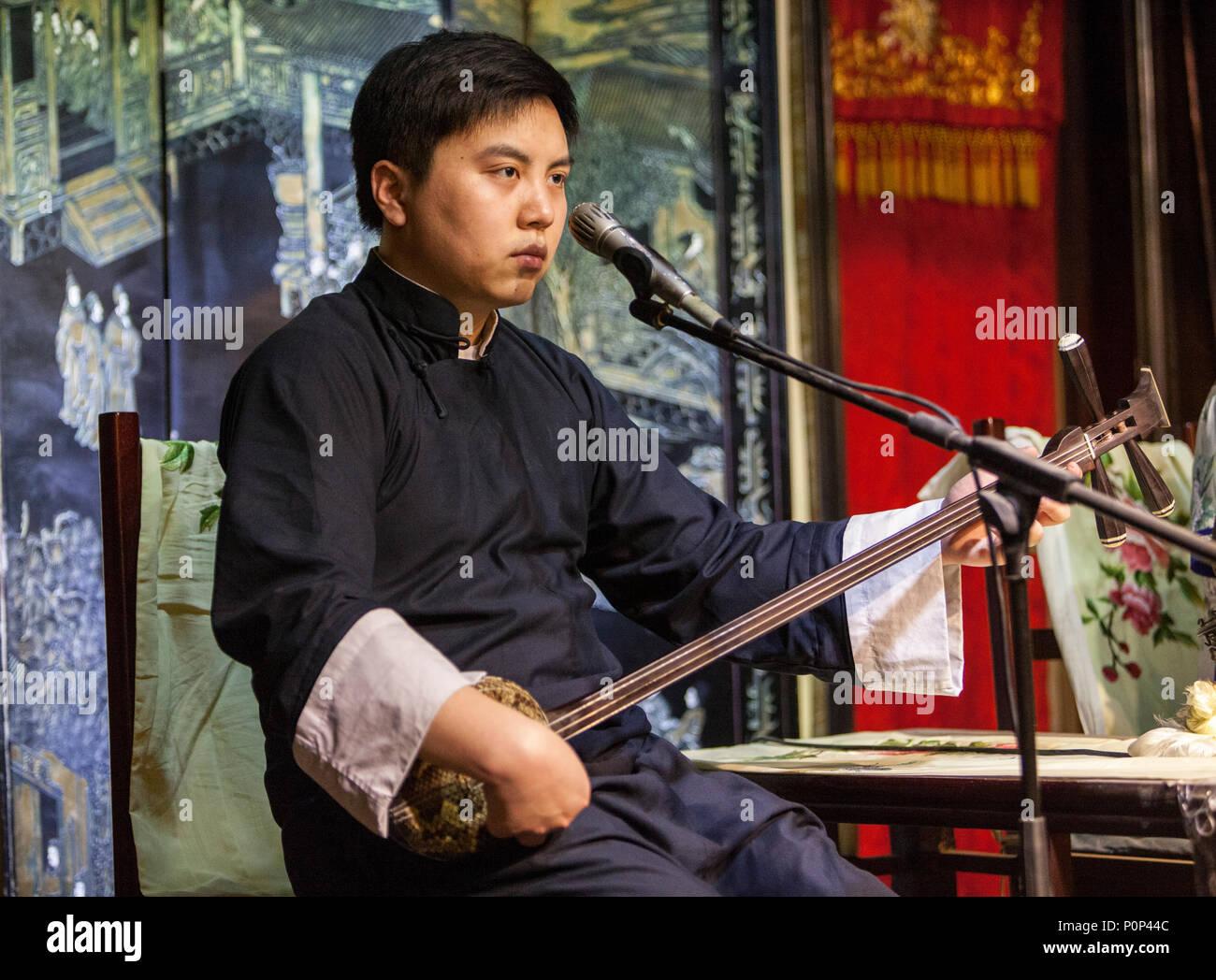 Suzhou, Jiangsu, China.  Young Man Playing a 'Three Strings.' - Stock Image